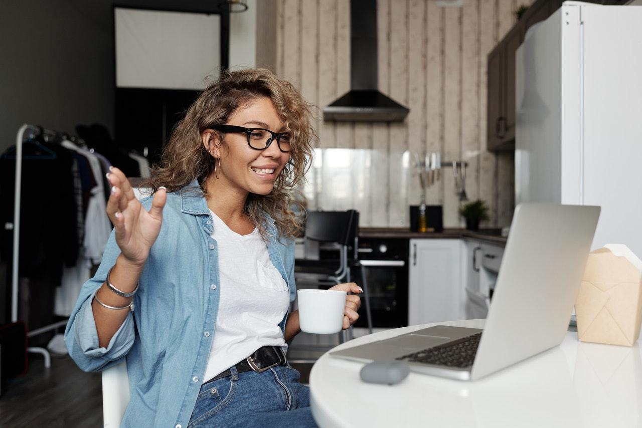 Dame drikker kaffe på arbejdet foran computeren